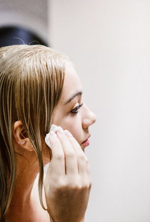hygienic: Girl applying lotion on face, daily skin care. Stock Photo