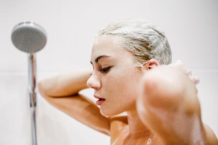 mujer bañandose: Hermosa joven tomando ducha en el baño