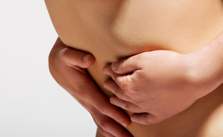 The close up photo of nude womans belly with stomach ache.