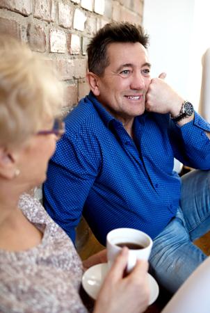 Smiling senior couple drink coffee or tea