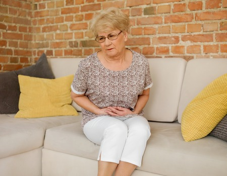 Senior woman having stomachache Stock Photo