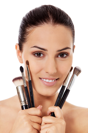 close up eyes: Beautiful face of young woman with make up brush. Stock Photo