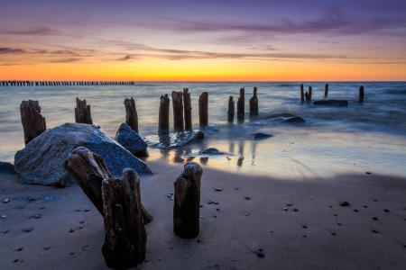 Stones and breakwater at sunset photo