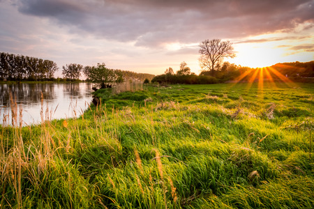 Sunset, river and sun rays photo