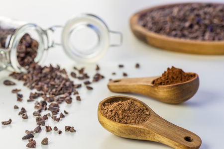 Cocoa beans and cacao powder - closeup with detail macro shot. Stock Photo