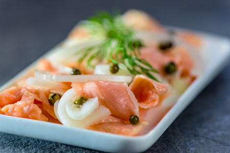Salmon in a marinade of lemon juice with green onion and pepper - healthy food - closeup Stock Photo