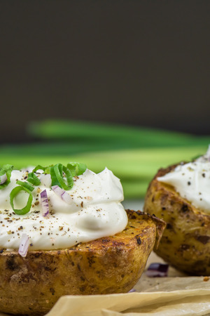 Baked potatoes with curd cheese, red onion and chive - closeup Foto de archivo