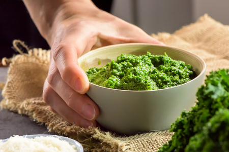 Hand holding pesto made from kale, grana cheese, lime, pine nuts and garlic - close up