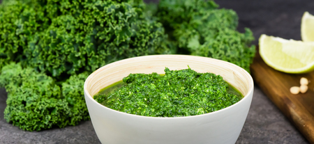 Pesto made from kale, cheese grana padano, lime, pine nuts and garlic - close up - banner