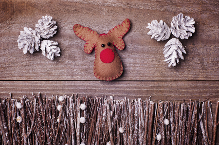 wooden reindeer: Handmade from felt Rudolph reindeer on wooden background. Craft arranged from sticks, twigs, driftwood and pine cones white and shiny. Stock Photo