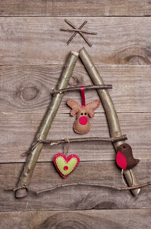 rudolph: Christmas tree arranged from sticks, twigs, driftwood on wooden background. Handmade red and green heart, Rudolph reindeer and robin made from felt hanging on tree. Craft.