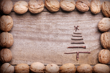 Twigs: Simple frame arranged from walnuts on wooden background with Christmas tree made from sticks, twigs, driftwood.