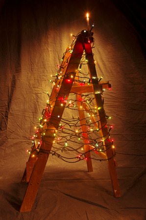 ladder: The wooden ladder decorated with Christmas lights. The shape of a Christmas tree with a lighted candle on the top. Stock Photo