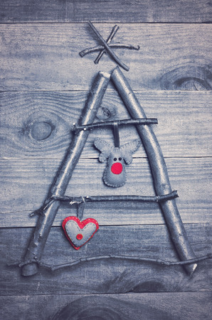 rudolph: Christmas tree arranged from sticks, twigs, driftwood on wooden background. Handmade red and green heart and Rudolph reindeer made from felt hanging on tree. Craft.