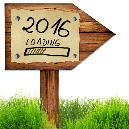 old page: Wood arrow sign with 2016 loading handwritten on old page of paper nailed to planks, green grass around, isolated on a white background. Stock Photo