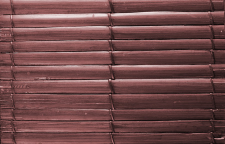 uniting: Bamboo sticks brown wooden background with thread uniting. Stock Photo