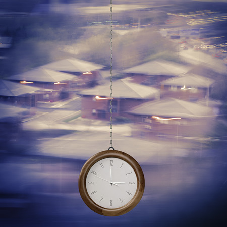 first time buyer: Time to Invest concept. Modern clock hanging on chain on blurred homes background.Time for home.