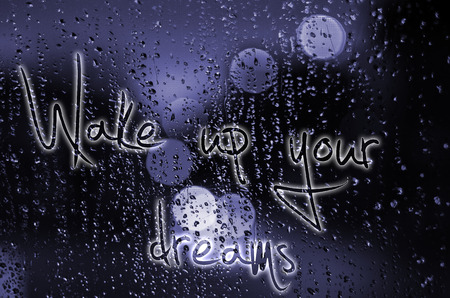 dreams of city: Sentence Wake up your dreams written on a wet glass. Night city life through windscreen: darkness and rain. Stock Photo