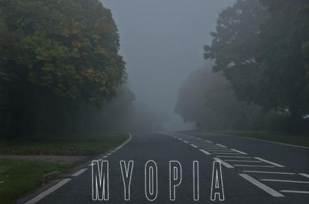 myopia: Word myopia written on foggy, blurred road, danger autumn road