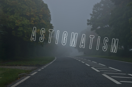 astigmatism: Word astigmatism written on danger road on a foggy day. Road through the autumn forest. Vision problem. Stock Photo
