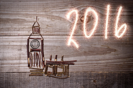 12 o'clock: Big Ban arranged from wooden sticks, clock showing 12 oclock. Sparkly 2016 written on grey background.