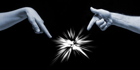 fingertip: Man and woman hands pointing on incomprehensible light on black background. Stock Photo