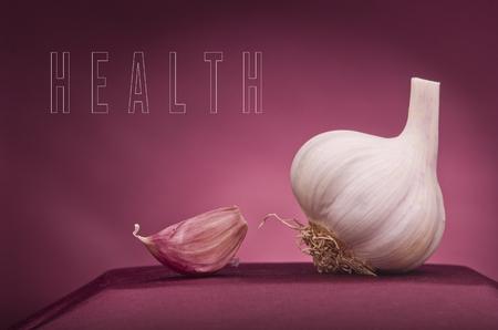 fresh garlic: Health word written on red background. Garlic as a sculpture.