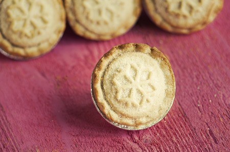 Festive shortcrust pastry mince pies. A sweet mince pie, a traditional rich festive food on red wooden background.
