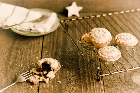 christmas cooking: Freshly homemade mince pies  on a cooling rack. Christmas traditional food on wooden background.