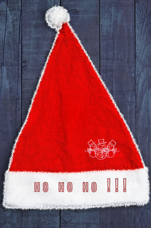ho: Santas red hat on blue wooden background. Snowman and HO HO HO text.