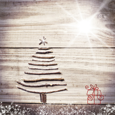 fir tree: Christmas tree arranged from sticks on wooden sparkly grey background. Bright star and present. Stock Photo