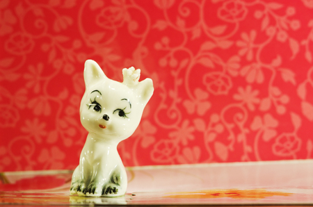 cat goddess: Ceramic figurine cute white cat on red background.