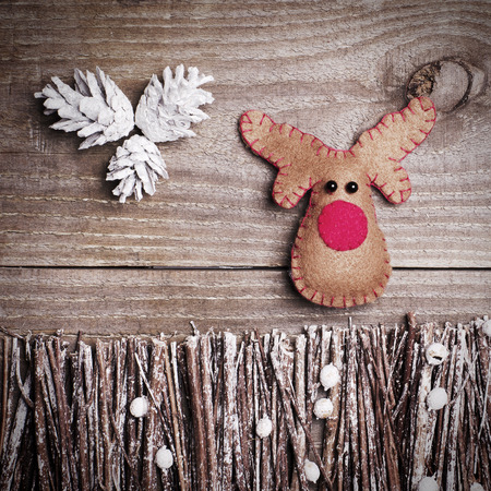 rudolph: Handmade from felt Rudolph reindeer on wooden background. Craft arranged from sticks, twigs, driftwood and pine cones white and shiny. Stock Photo