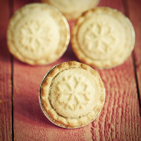 carne picada: Festive shortcrust pastry mince pies. A sweet mince pie, a traditional rich festive food on red wooden background.
