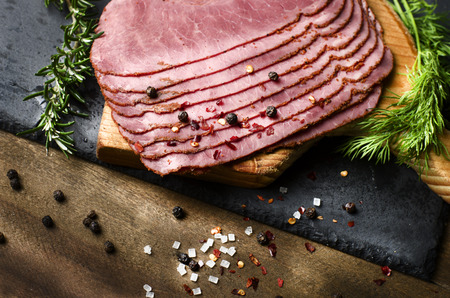 fresh sliced beef pastrami surrounded by herbs in wooden chopping board Stock Photo