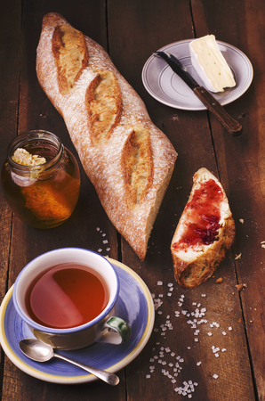 crusty french bread: Slice of homemade fresh baguette with jam, plate with cheese, jar of natural honey and cup of tea on wooden table.