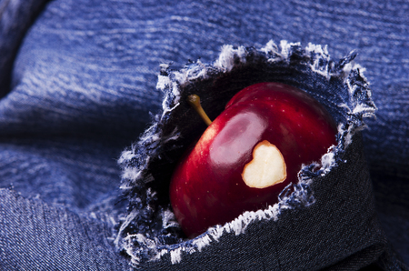 apple gmo: Ripe apple with heart on jeans background, close-up. Healthy eating, life concept.  GMO free genetically modified organisms. Valentines day.