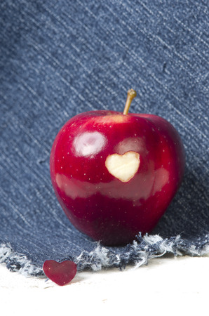 genetically modified organisms: Fresh red apple with a heart shaped cut-out on jeans background. GMO free genetically modified organisms. Valentine day.
