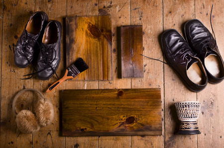 footware: Natural wooden planks with copy space on wooden floor background. Two pair of black shoes, small drum and cosy earmuffs. Stock Photo