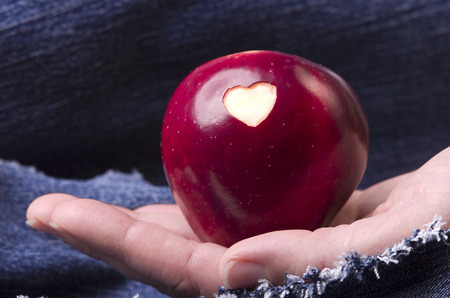 denim: Fresh red apple with a heart shaped cut-out in woman hand on denim, jeans background. GMO free genetically modified organisms. Mothers day