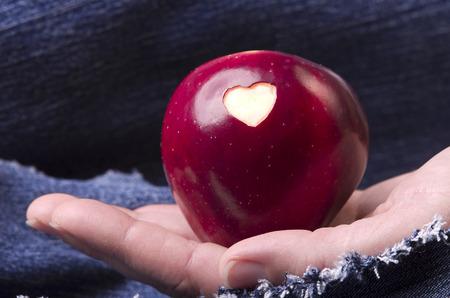 mezclilla: Manzana roja fresca con un corazón en forma de agujero en mano de la mujer en dril de algodón, vaqueros de fondo. Sin OGM organismos genéticamente modificados. Día de la Madre Foto de archivo