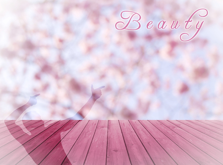 feminine background: Beauty written on empty perspective wood over blurred, blooming trees with bokeh background, for product display montage. Shadow of a man pointing on beauty.