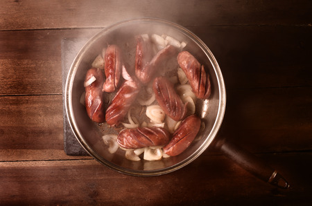 cook out: Fried sausage with onion. Lid removed right before shooting, natural steam. Stock Photo