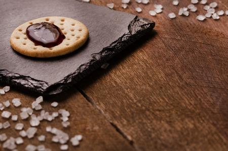 Cracker con marmellata sulla parte superiore su pietra nera, granella di zucchero su sfondo di legno. Copia spazio