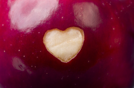 apple gmo: Fresh red apple with a heart shaped cut-out close-up. Healthy eating, life concept.  GMO free genetically modified organisms. Valentines day.