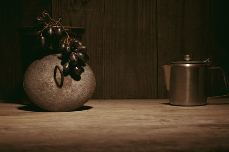percolator: Coffee percolator, black grapes on wooden table, copy space. Stock Photo