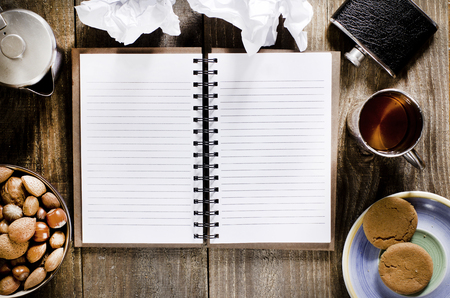 hip flask: An open notebook with blank pages on wood table.Cup of tea,  hip flask,nuts and biscuits snack. Stock Photo