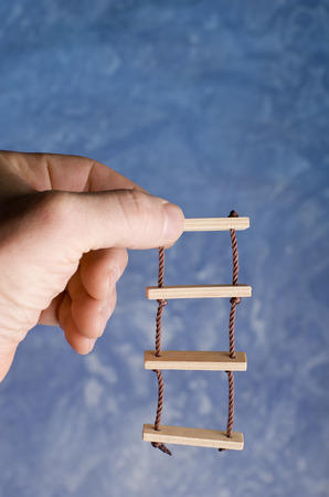 rope ladder: Rope ladder toy holding in adult hand on blue background. Climbing for success imaginations. Stock Photo
