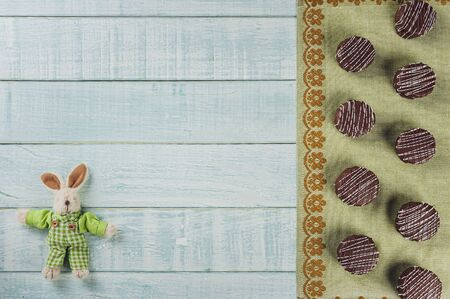 Top view of brazilian home made honey cookies chocolate covered on wooden background with stuffed rabbit and copy space - Pães de mel