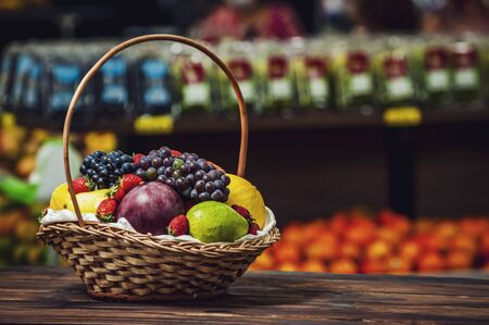 Basket and fresh fruits on wooden table at the market